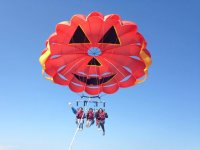 three people on a parascending parachute