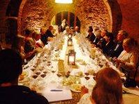 grupo de personas disfrutando de una cata de vino en una bodega