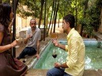 tres personas bebiendo una copa de vino en una fuente