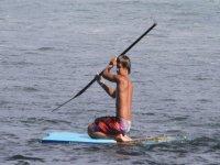 孩子在跪板上和一个划船在手上