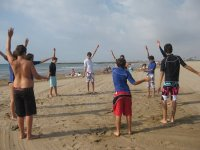chicos calentando en la arena de la playa