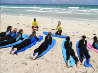 chicos en las tablas de surf sobre la arena escuchando a su profesor.JPG