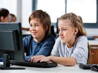 dos ninos escribiendo en el teclado de un ordenador