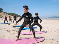 ninos aprendiendo a surfear sobre la arena