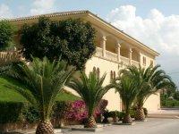 una casa grande rodeada de palmeras y jardines verdes