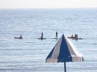 Dalla spiaggia guardando come praticano il paddle surf