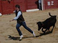 hombre corriendo mientras una vaquilla le sigue