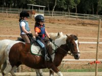 two girls riding horses in a closed enclosure