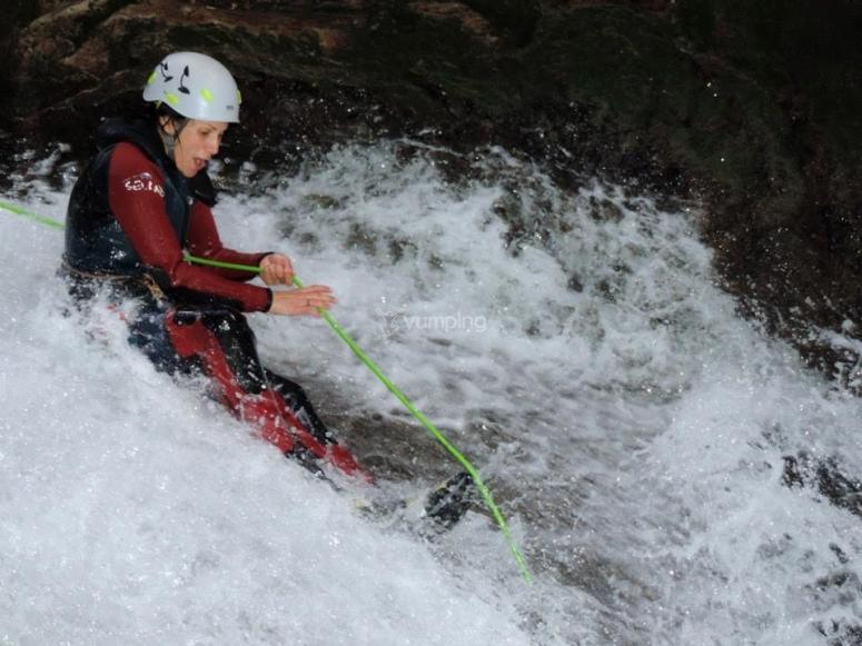 mujer practicando barranquismo en aguas bravas
