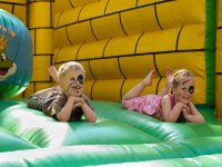 children with painted faces lying in an inflatable castle