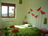 dos camas con colchas verdes y flores en las paredes