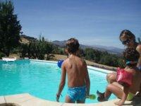 dos ninos en el borde de una piscina infantil junto a la monitora