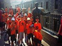 ninos con gorras y camisetas naranjas de excursion