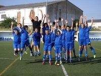 ninos saltando con los brazos levantados en un campo de futbol