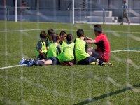 ninos sentados en el cesped junto a su entrenador