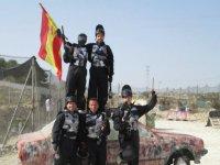 一群男孩与西班牙国旗旁边一辆废弃的汽车 - 伪装成一名军人,头盔武器和军装