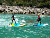 Passing the rapids with the paddle surf boards