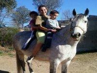 madre con dos niños montando a caballo