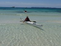 dos personas en kayak en la orilla del mar