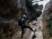 Rappeling supporting your feet on the rock
