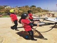 Niños preparando el material de windsurf