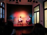 一个年轻的女孩和一个女人在舞台上坐在椅子上