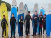 children next to surfboards