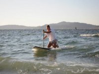 young man practicing paddle surfing