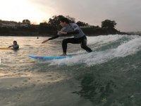 Alumno de surf sobre la ola