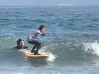 Joven surfeando junto al profe