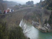 personas cruzando un puente de piedra