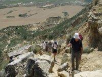 personas subiendo por una montana de piedra