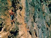 chico sin camiseta escalando por una pared vertical