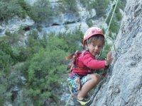 nino escalando con un casco y cuerdas