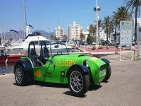 coche verde electrico biplaza con el puerto de fondo