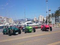 tres garbis aparcados con un puerto de fondo