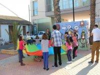 ninos con un gran paracaidas jugando