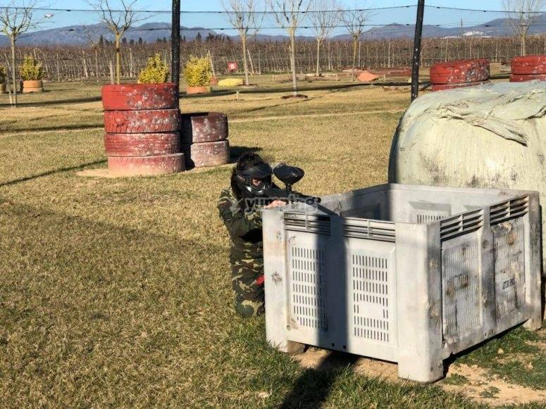 Behind the paintball field barricade