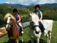 Children riding a pony in Montseny