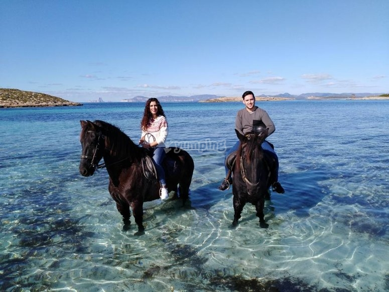 Pareja a caballo en el mar en Formentera