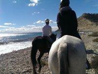 Pareja a caballo al lado del mar