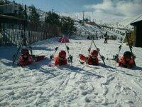 Saludando在雪地里躺在雪地儿童滑雪场