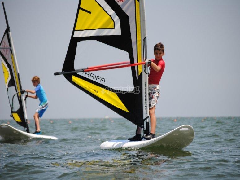 Niños practicando windsurf