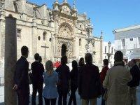 人们在教堂前面的树荫下