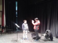 two people on a stage with a music stand