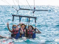 Sitting in the harness attached to the parasail wing