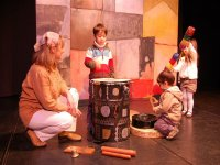 children playing on a stage with musical instruments