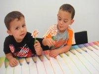 dos ninos apoyados en una mesa con dibujos de lapices
