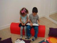 dos ninos sentados en un sillos leyendo