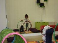 ninos jugando con aros de colores delante de un espejo